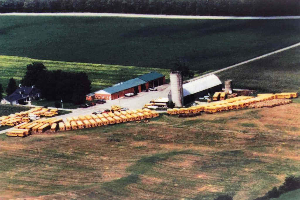 Aerial view of a vast bus fleet parked at the Sharp Bus Lines Farm