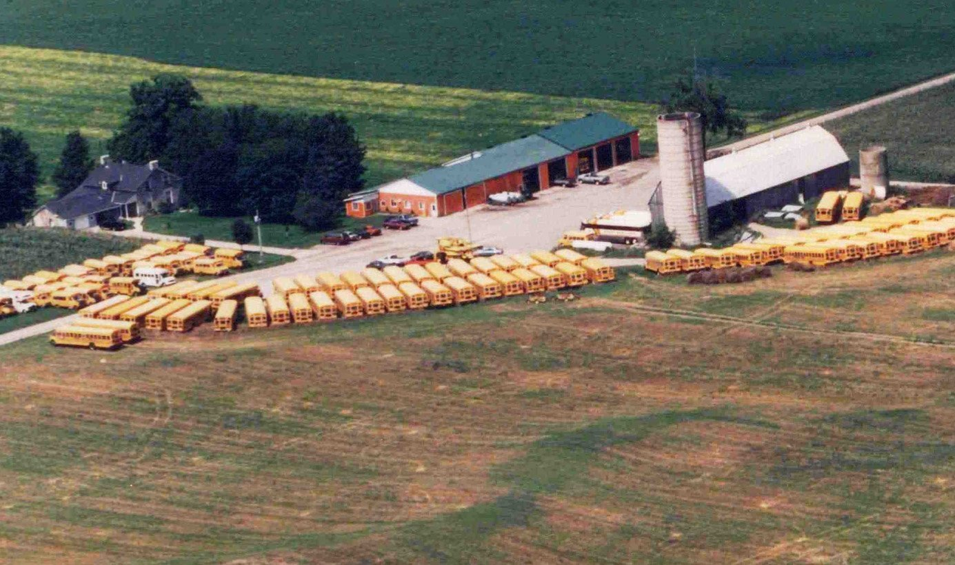 Aerial view of original Sharp farm with many buses parked around the property